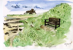 A seat on the right backed by a steep bank is swathed in tall grasses. To the left behind the brow of the slope is Bamburgh Castle and its beach.