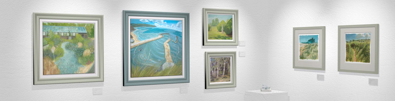 Original landscape paintings hang on a wall in a gallery